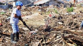 Un funzionario dell'UNDP sta pulendo le macerie in un villaggio di pescatori, Barangay, Filippine