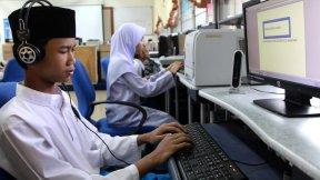 Un adolescente utilizza un software text-to-speech per far funzionare un computer in una scuola speciale di Kuala Lumpur, in Malesia.