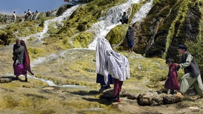 La foto ritrae delle famiglie che passeggiano serenamente tra le cascate e i prati di Band-e-Amir, il primo parco nazionale in Afghanistan