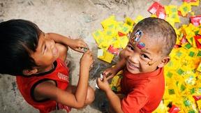 Due bambini giocano con l'immondizia e con adesivi colorati
