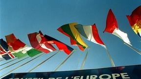 """Fotografia di un'insegna con la scritta """"Conseil de l'Europe"""" con delle bandiere sovrastanti di alcuni degli stati membri."""