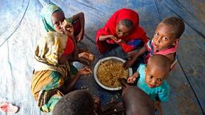 Un gruppo di bambini rifugiati mangia in una tenda a Dollo Ado, Etiopia, 2011