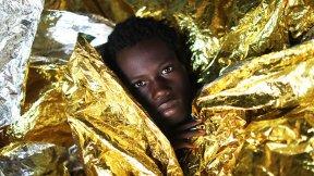 Bambino migrante della Guinea con coperte termiche a seguito di un'operazione di salvataggio in mare da parte di una ONG spagnola