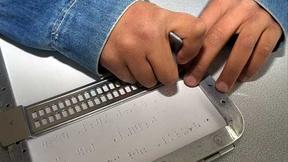Primo piano di due mani di un bambino mentre scrivono in Braille con l'ausilio di una tavola tattile.