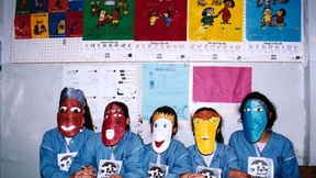 Bambini con una maschera che riprende caratteristiche somatiche e culturali di diverse etnie.