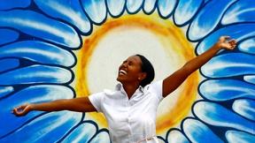 Una donna posa di fronte ad un graffito che rappresenta un Sole