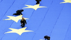 Four workers laying down 4 of the 12 stars of a large representation of the flag of the Council of Europe during a celebration.