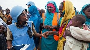 Agente di polizia donna interagisce con le donne residenti nel campo per sfollati Zam Zam, vicino a El Fasher, capitale del Nord Darfur.