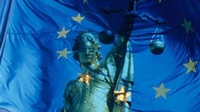 Un'allegoria della giustizia si sovrappone alla bandiera dell'UE