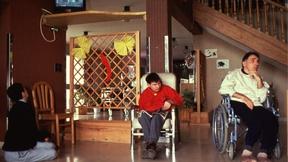 Persone con disabilità in carrozzella all'interno di una struttura ricreativa.
