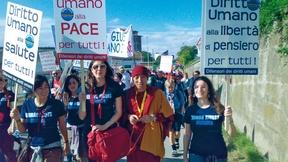 """Studenti dei Corsi di laurea sui diritti umani dell'Università di Padova alla Marcia per la Pace Perugia-Assisi """"Tutti i diritti umani per tutti"""", 7 ottobre 2007. Alcune ragazze camminano assieme ad un monaco tibetano portando dei cartelli che enunciano ciascuno un diverso diritto umano."""