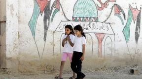 Due ragazzine passeggiano nel campo profughi palestinese di Acqba Jaber gestito dall'Agenzia delle Nazioni Unite per il Soccorso e l'Occupazione, accanto ad un muro su cui è raffigurata una moschea riportante i colori palestinesi.