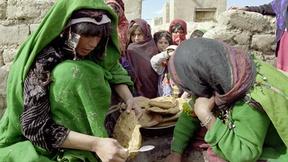 Donne afgane preparano un pasto sotto gli occhi dei propri bambini all'interno del campo profughi di Maslakh