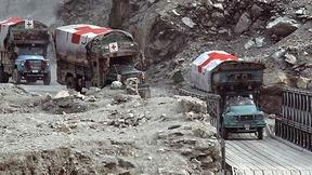 Camion della croce rossa in fila in una zona di conflitto