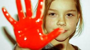 """Foto di una bambina che mostra la mano colorata di rosso, nell'ambito della campagna """"Red Hand"""" promossa da numerose ONG internazionali per richiedere una più forte azione contro l'uso dei bambini soldato, 2009."""