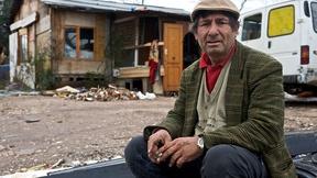 Uomo appartenente all'etnia Rom seduto davanti ad un alloggio fatiscente. Foto scattata durante la visita del Commissario Hammarberg (CoE) nel 2009.