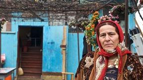 Donna appartente all'etnia Rom davanti ad una casa fatiscente. Foto scattata durante la visita del Commissario Hammarberg (CoE) nel 2009.