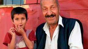 """Foto di un bambino e di un anziano di etnia Rom. Campagna del Consiglio d'Europa """"Dosta!"""""""