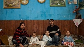 The picture shows a Roma family composed by father, mother and three children who are sat on big cushions inside their home