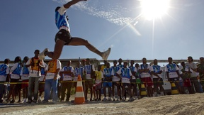 Spettatori guardano un giovane haitiano levarsi in volo per il suo salto in lungo