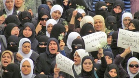 Syrian women protest showing placards