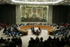 A UN Security Council session. The participants are seated around a circular table, in the center of which is positioned another, rectangular table.