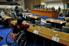 Tavoli predisposti in una sala convegni per accogliere persone che utilizzano sedie a rotelle; sul fondo della sala il tavolo dei relatori.