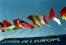"""A sign with the text """"Conseil de l'Europe"""" in French, with the flags of some member states hanging above."""